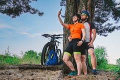 Lyckliga par med mountainbiket som utomhus tar selfiesmartphonen Ett lyckligt par, som leder en aktiv livsstil som stoppas i royaltyfria foton