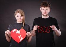 Lyckliga par med murbrukhjärta och sos-ord Arkivfoton
