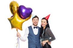 Lyckliga par med partilock och ballonger royaltyfri fotografi