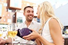 Lyckliga par med plånboken som betalar räkningen på restaurangen Royaltyfria Bilder