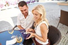 Lyckliga par med plånboken som betalar räkningen på restaurangen Arkivfoto