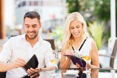 Lyckliga par med plånboken som betalar räkningen på restaurangen Arkivbilder
