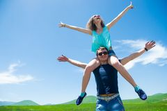 Lyckliga par med öppna armar, flickasammanträde på skuldraman Arkivbilder