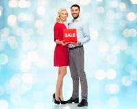 Lyckliga par med röd försäljning undertecknar över blåa ljus Arkivfoto