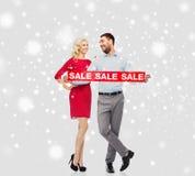 Lyckliga par med röd försäljning undertecknar över snö Arkivfoto