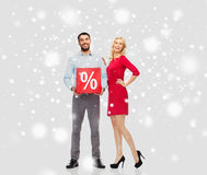 Lyckliga par med röd försäljning undertecknar över snö Arkivbild