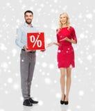 Lyckliga par med röd försäljning undertecknar över snö Royaltyfria Foton