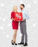 Lyckliga par med röd försäljning undertecknar över snö Royaltyfria Bilder