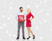 Lyckliga par med röd försäljning undertecknar över snö Arkivfoton