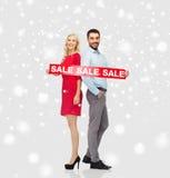 Lyckliga par med röd försäljning undertecknar över snö Royaltyfri Bild