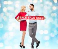 Lyckliga par med röd försäljning undertecknar tänder över Royaltyfri Fotografi
