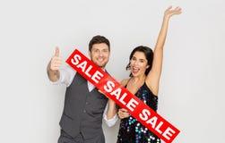 Lyckliga par med röd försäljning undertecknar upp visningtummar Royaltyfri Fotografi
