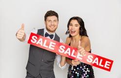 Lyckliga par med röd försäljning undertecknar upp visningtummar Fotografering för Bildbyråer