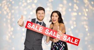 Lyckliga par med röd försäljning undertecknar upp visningtummar Arkivfoto