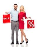 Lyckliga par med röda shoppingpåsar Royaltyfri Foto