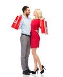 Lyckliga par med röda shoppingpåsar Arkivfoton