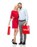 Lyckliga par med röda shoppingpåsar Royaltyfria Foton