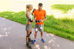 Lyckliga par med rullskridskor som utomhus rider Arkivfoton