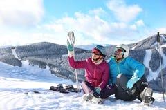 Lyckliga par med skidar utrustning som sitter på den snöig kullen i berg, utrymme för text arkivfoton