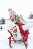 Lyckliga par med släden i vinter royaltyfri bild