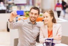 Lyckliga par med smartphonen som tar selfie i galleria Royaltyfri Bild