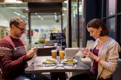 Lyckliga par med smartphones på strikt vegetarianrestaurangen Fotografering för Bildbyråer