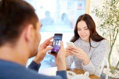 Lyckliga par med smartphones som dricker te på kafét Arkivbilder
