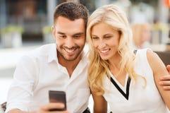 Lyckliga par med smatphone på stadsgatakafét Royaltyfria Bilder