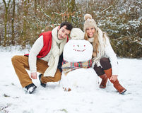 Lyckliga par med snögubben i vinter Arkivfoton