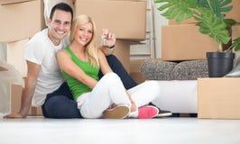 Lyckliga par med tangent av det nya hemmet