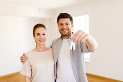 Lyckliga par med tangenter av det nya hemmet Royaltyfria Bilder