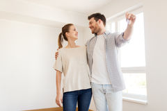 Lyckliga par med tangenter av det nya hemmet Royaltyfri Foto