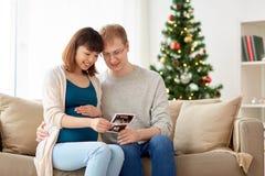 Lyckliga par med ultraljudbilder på jul Arkivbilder