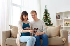 Lyckliga par med ultraljudbilder på jul Royaltyfria Bilder