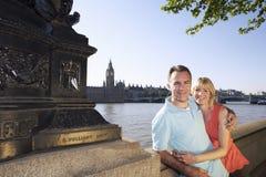 Lyckliga par mot Thames River fotografering för bildbyråer