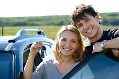 Lyckliga par near den nya bilen Arkivbilder