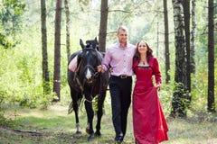 Lyckliga par och häst Royaltyfri Bild