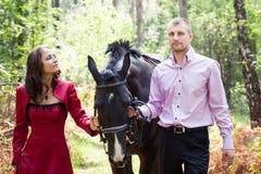 Lyckliga par och häst Royaltyfria Bilder
