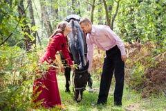 Lyckliga par och häst Arkivfoto