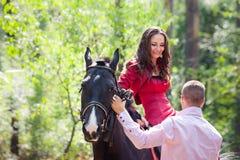 Lyckliga par och häst Royaltyfri Foto