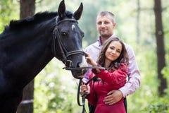 Lyckliga par och häst Arkivbilder