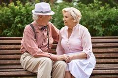 Lyckliga par på bänk Fotografering för Bildbyråer