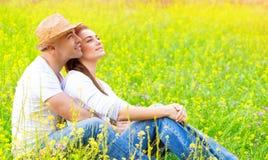 Lyckliga par på blom- fält Fotografering för Bildbyråer