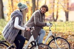 Lyckliga par på cyklar i skog under nedgångtid royaltyfria foton