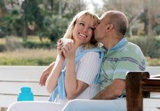 Lyckliga par på en bänk arkivbilder