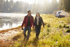Lyckliga par på en campa tur som går nära en sjö arkivbilder
