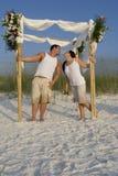 Lyckliga par på en strand fotografering för bildbyråer
