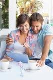Lyckliga par på ett datum genom att använda minnestavlaPC Fotografering för Bildbyråer
