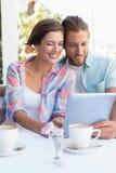 Lyckliga par på ett datum genom att använda minnestavlaPC Royaltyfri Fotografi