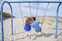 Lyckliga par på gungor Arkivfoton